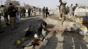 مأموران امنیتی پاکستان در حال بازدید از محل انفجار بمب.