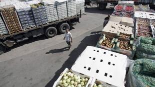 Caminhões carregados de frutas e verduras atravessam posto de controle israelense no sul da Faixa de Gaza.