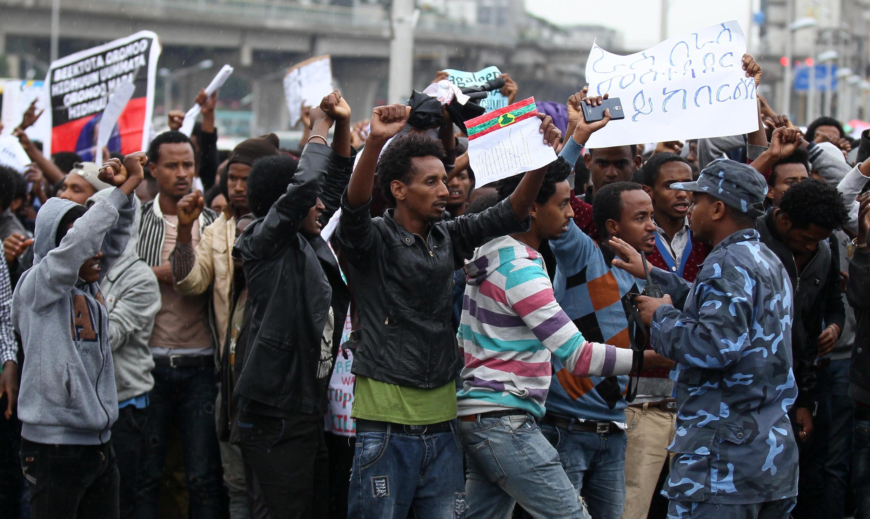 Un policier tente de calmer des manifestants qui défilent contre le gouvernement éthiopien, le 6 août 2016.