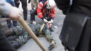 Один из участников протеста, раненый в стычке с милицией в Киеве 18/02/2014 (архив)