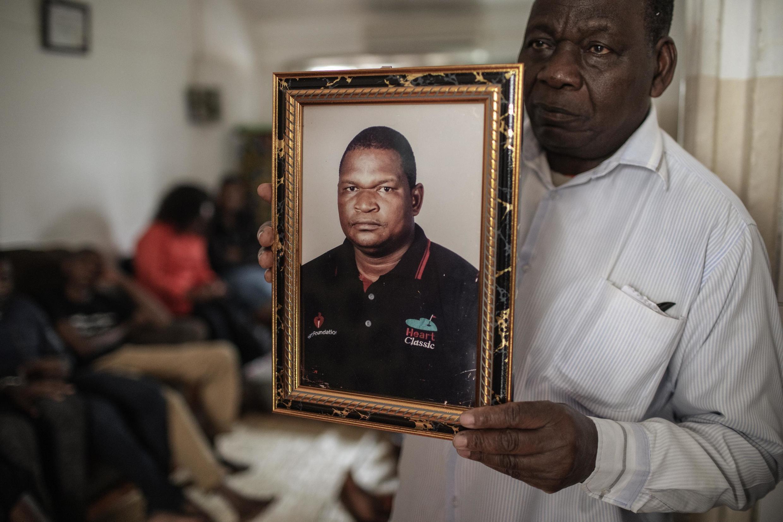 Filipe Mahajane, porta-voz da família Matavele, com um retrato de Anastácio Matavele. Xai-Xai, 11 de Outubro de 2019.