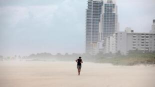 Homem enfrenta o vento nas praias de Miami pouco antes da passagem do furacão Matthew.