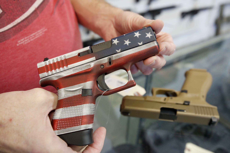 A worker restocks handguns at Davidson Defense in Orem, Utah on March 20, 2020