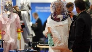 A visitor looks at chemical protective suits at the World Nuclear Exhibition in Le Bourget near Paris, 14 October, 2014