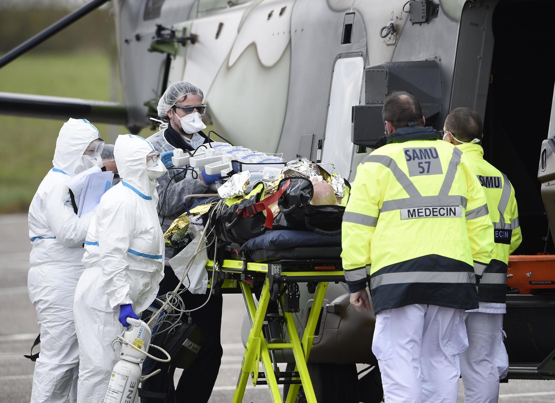 Du personnel soignant évacue un malade du Covid-19 de l'Hôpital de Metz vers celui d'Essen en Allemagne, le 29 mars 2020.