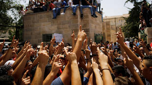 Des Palestiniens célèbrent la décision des autorités israéliennes tout près de la vieille ville de Jérusalem, ce jeudi 27 juillet.
