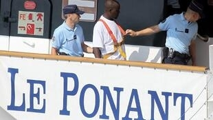 Deux gendarmes français encadrent un pirate présumé lors de la reconstitution de la libération de l'équipage du Ponant, le 17 juillet 2010.