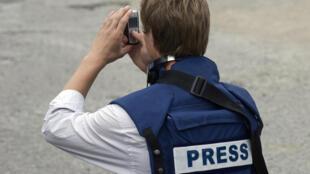 Un journaliste consulte son téléphone portable dans une zone de guerre.
