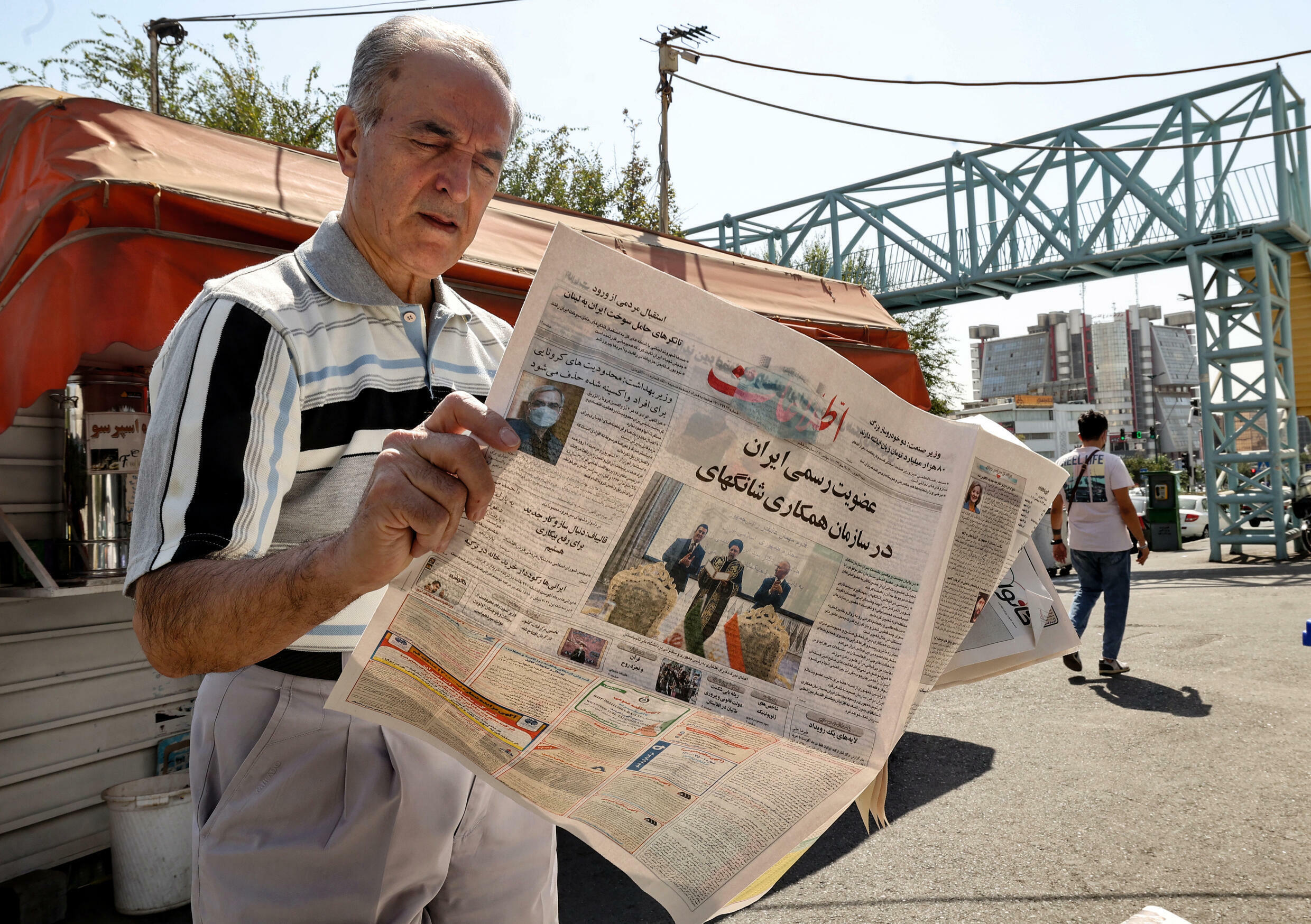 """An Iranian man reads a copy of the daily newspaper """"Etalaat"""" headlined, """"Iran is a new member of the Shanghai Cooperation Organisation"""", at a kiosk in Tehran on September 18, 2021"""