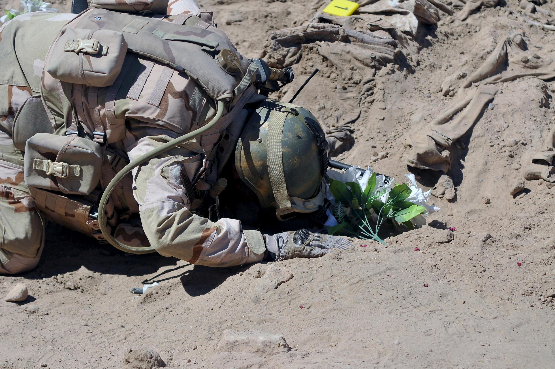 Солдат на обнаруженном массовом захоронении убитых новобранцев, апрель 2015 г.