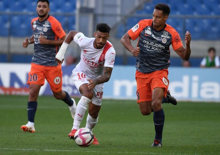 Nimes' French midfielder Denis Bouanga (C) vies with Montpellier's French defender Daniel Congre (R) during the match
