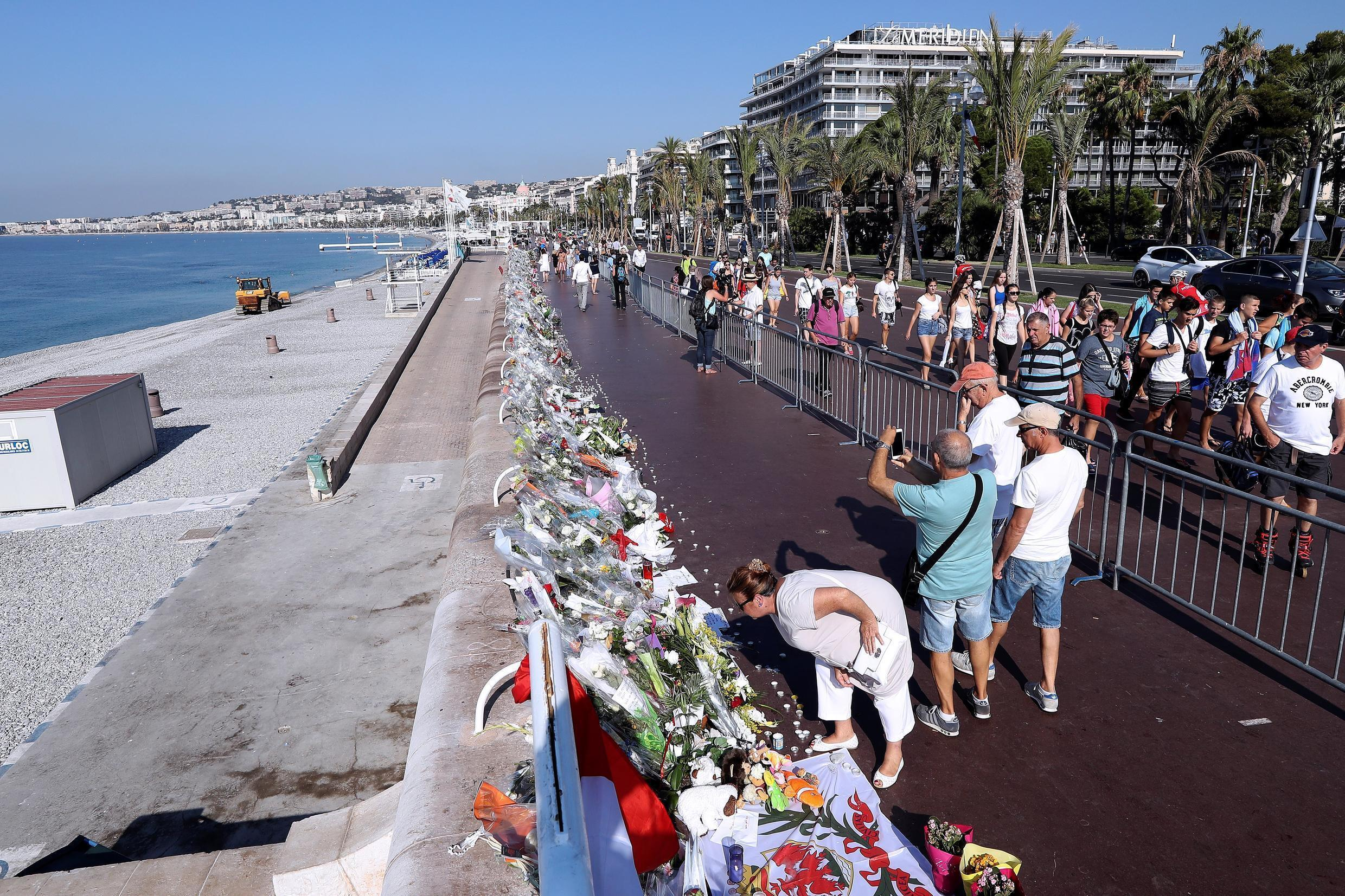 This file picture shows people standing by the makeshift memorial in tribute to the victims of the terror attack in Nice.
