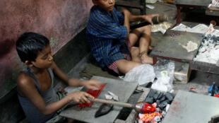 Des enfants indiens travaillent dans une petite usine de moulage de plastique à Howrah, dans l'Etat du Bengale-Occidental, dans le nord-est de l'Inde.