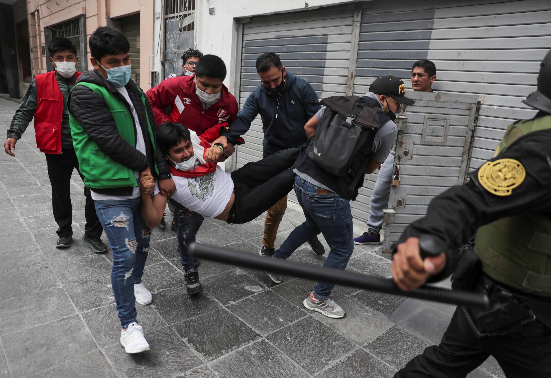 Un hombre observa como oficiales de civil detienen a un hombre durante las protestas después de que el presidente interino de Perú, Manuel Merino, prestó juramento tras la destitución del presidente Martín Vizcarra, en Lima.