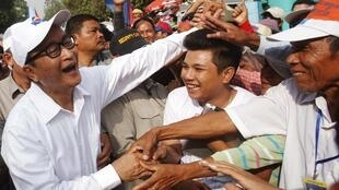 Sam Rainsy, leader du CNRP, parti de l'opposition, serre les mains de ses partisans dans les rues de Phnom Penh, le 25 octobre 2013.