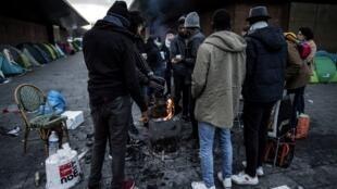 Imigrantes principalmente se aquecem próximo a um braseiro com uma refeição oferecida por voluntários da associação 'Solidarite migrants Wilson', em Saint-Denis, onde viviam em um acampamento improvisado.