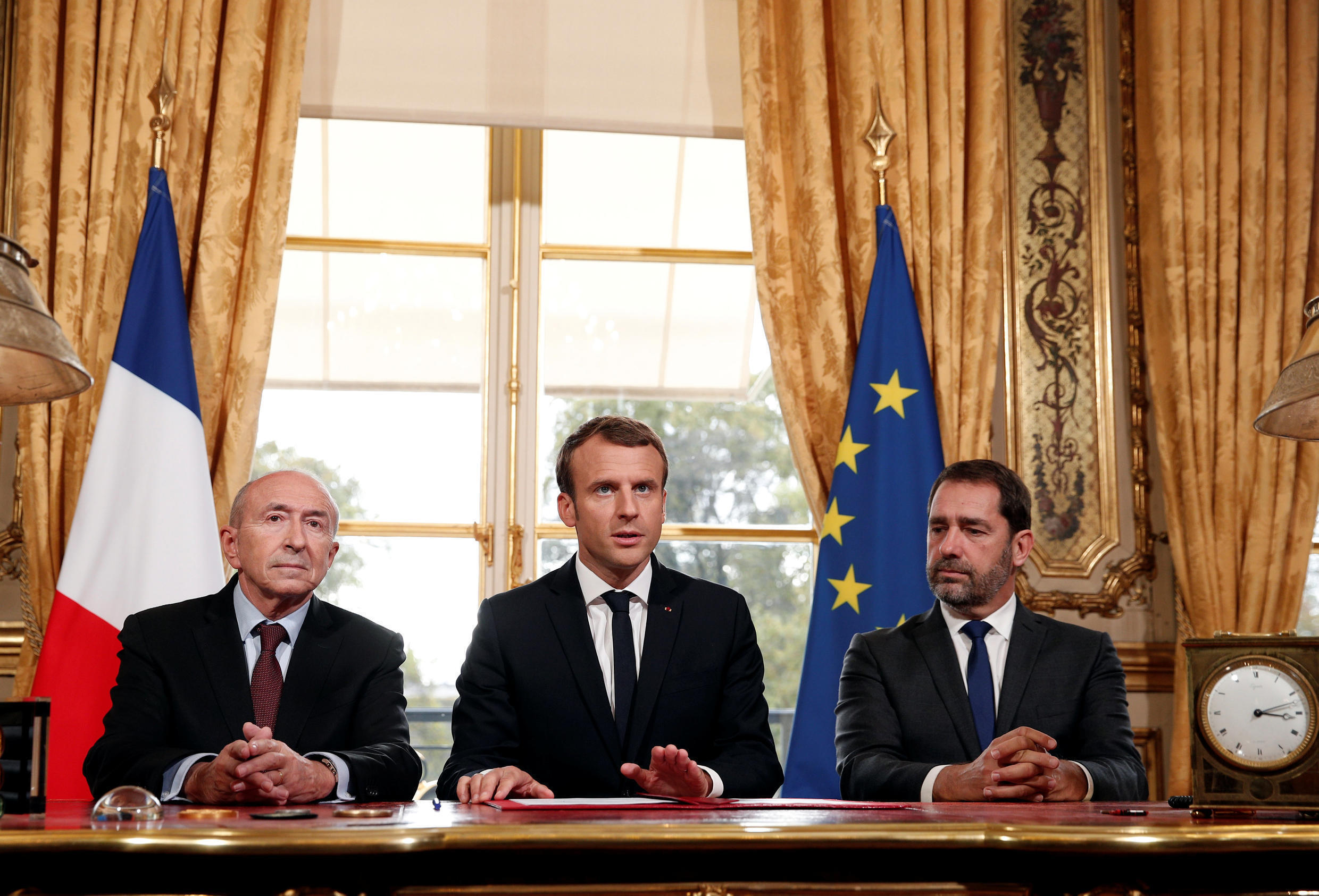 French President Emmnauel Macron (C) addresses the medias with French Interior Minister Gerard Collomb (L) and government spokesman Christophe Castaner after signing a new anti-terrorism and interior security law at the Elysee Palace in Paris, October 30.