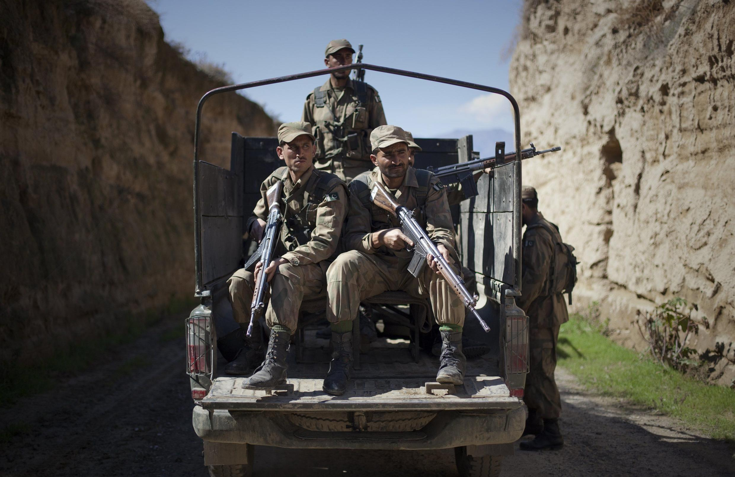 Pakistani soldiers keep guard along a road in Damadola, located in Bajaur Agency, in the country's tribal belt