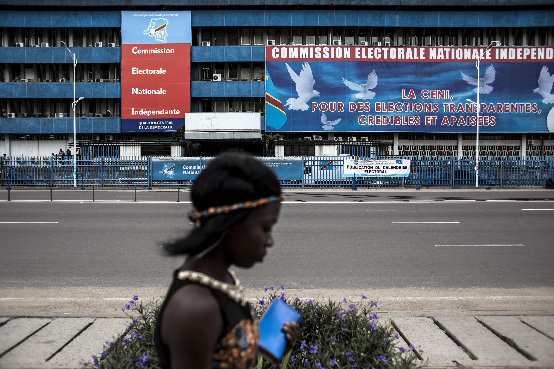 Uma mulher caminha diante da sede da Comissão Eleitoral Nacional Independente (CENI). Foto ilustração