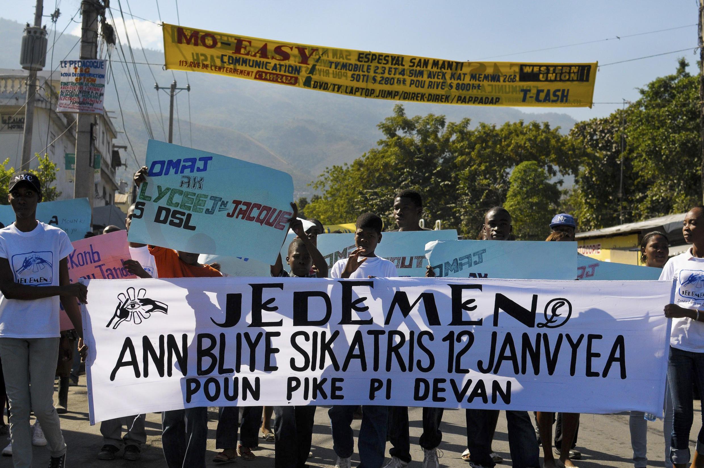 """Gente en Haití conmemorando los dos años del terremoto: """"No olvidemos el 12 de enero mientras avanzamos""""."""