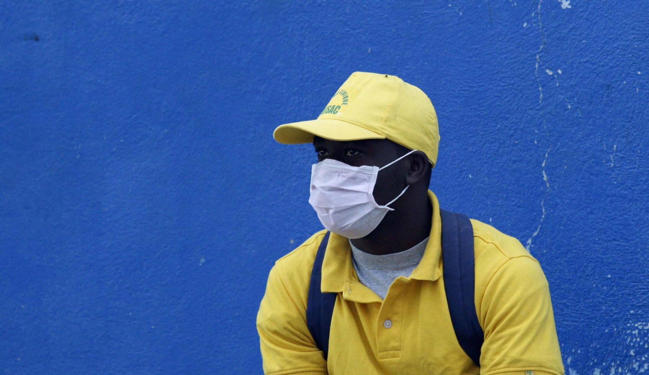 A man covers his face with a medical mask to prevent infections on a street in Port-au-Prince, Haiti