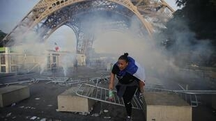 Teargas under the Eiffel Tower as police battle fans outside the fanzone, which was packed to capacity