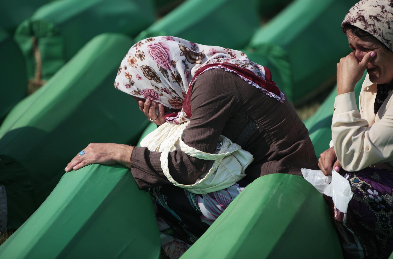 Bosnian Muslim women cry near coffins prepared for a mass burial at the Memorial Center in Potocari, near Srebrenica July 11, 2011.