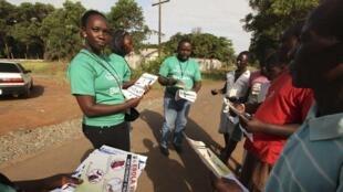 Des bénévoles distribuent des brochures qui expliquent comment éviter de contracter le virus Ebola.