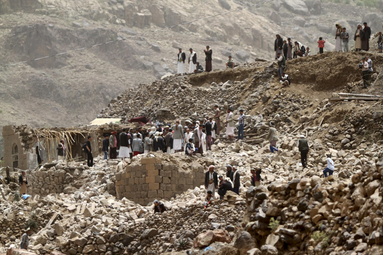 Moradores do vilarejo de Okash, perto da capital iemenita, em meio aos destroços provocados pelos ataques aéreos.