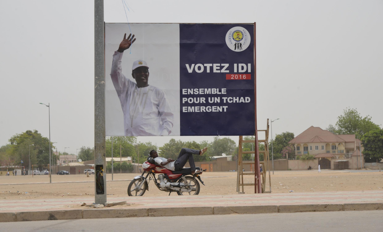 Un homme se repose devant une affiche de campagne du président tchadien Idriss Déby Itno, à N'djamena, le 12 avril 2016, deux jours après le premier tour de l'élection présidentielle.