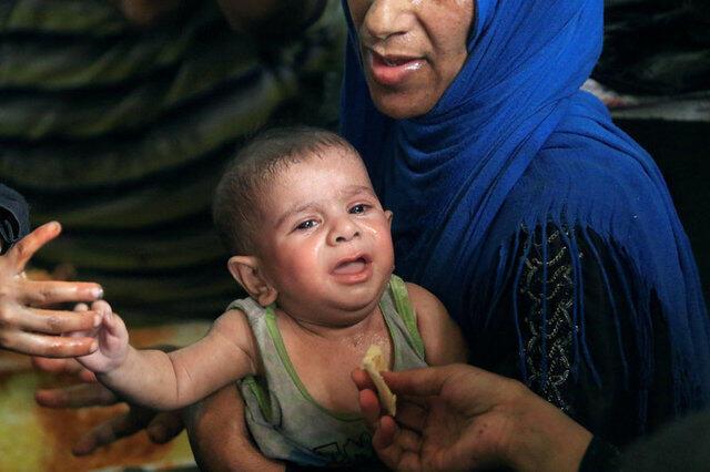 Mãe e criança são socorridas por ONGs e soldados ao final da batalha de Mossul, no Iraque.