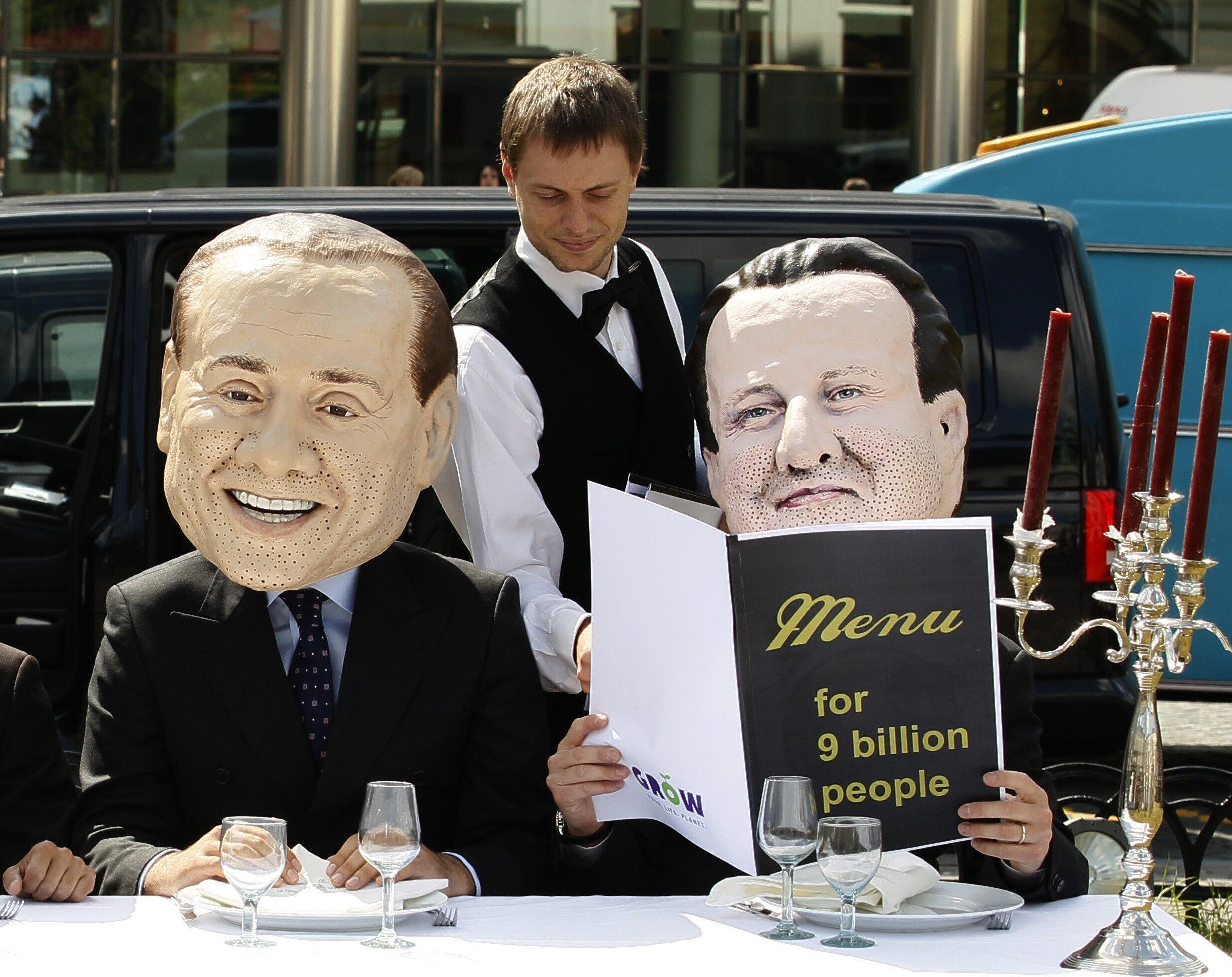"""Các nhà hoạt động Oxfam mang mặt nạ 2 thủ tướng Ý (Berlusconi, trái) và Anh (Cameron, phải), trong một cuộc biểu tình phản đối, mang tên """"Một bữa tối đủ cho 9 triệu người"""", trước nhà Quốc hội Châu Âu, 1/6/2011."""