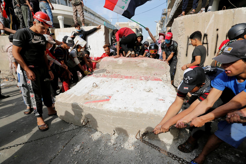 Des manifestants font tomber une partie d'un des murs installés près des institutions par le gouvernement, le 7 novembre 2019.