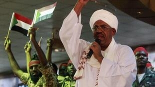 Supporters wave Sudanese flags as Sudanese President Omar al-Bashir addresses supporters during a rally at the ruling National Congress Party