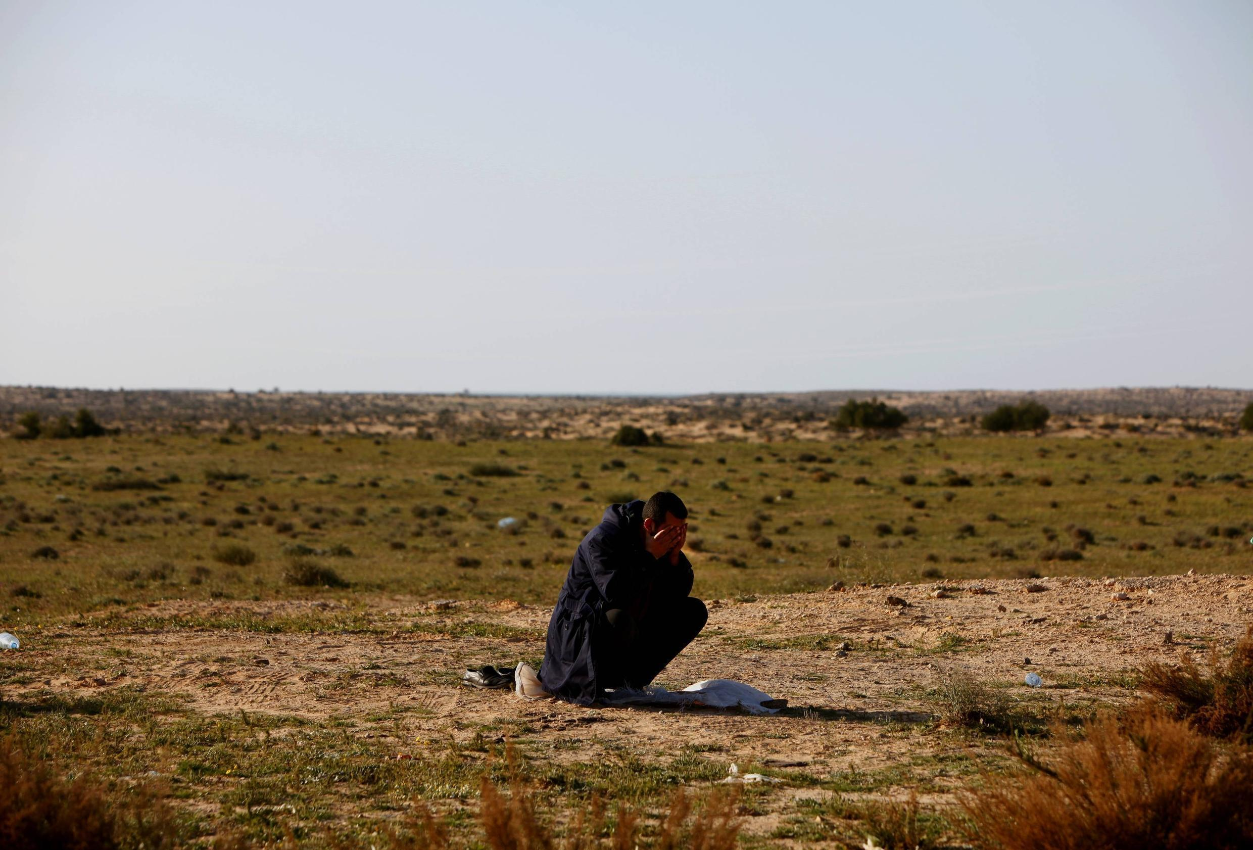 An Egyptian refugee prays shortly after crossing into Tunisian soil fleeing violence in Libya 25 February 2011