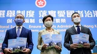 La jefa del ejecutivo de Hong Kong, Carrie Lam, y dos miembros de su gobierno posan para las cámaras antes de una rueda de prensa, el 30 de marzo de 2021 en la ciudad china
