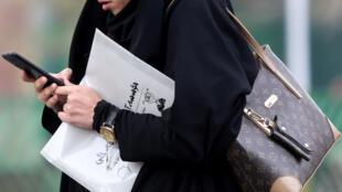 Mulher iraniana usa telefone celular em 23 de novembro de 2019. Autoridades iranianas cortaram o acesso à Internet durante as manifestações.