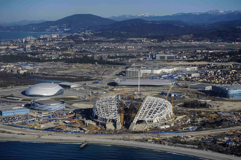 Vista aérea mostra estádio olímpico sendo construído em Sochi. Enquanto Moscou e outras cidades sofrem com excesso de neve, balneário só tem neve nas montanhas.