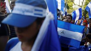 Centenares de personas, en su mayoría jóvenes vestidos de negro portando velas y banderas de Nicaragua, se congregaron en la noche del miércoles a una rotonda del sur de Managua.