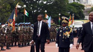Le président Alassane Ouattara (d) passe en revue la garde d'honneur accompagné du chef d'état-major des armées Soumaïla Bakayoko, au palais présidentiel à Abidjan, le 7 août 2016. Le chef de l'Etat a limogé le général Soumaïla Bakayoko le 9 janvier 2017.