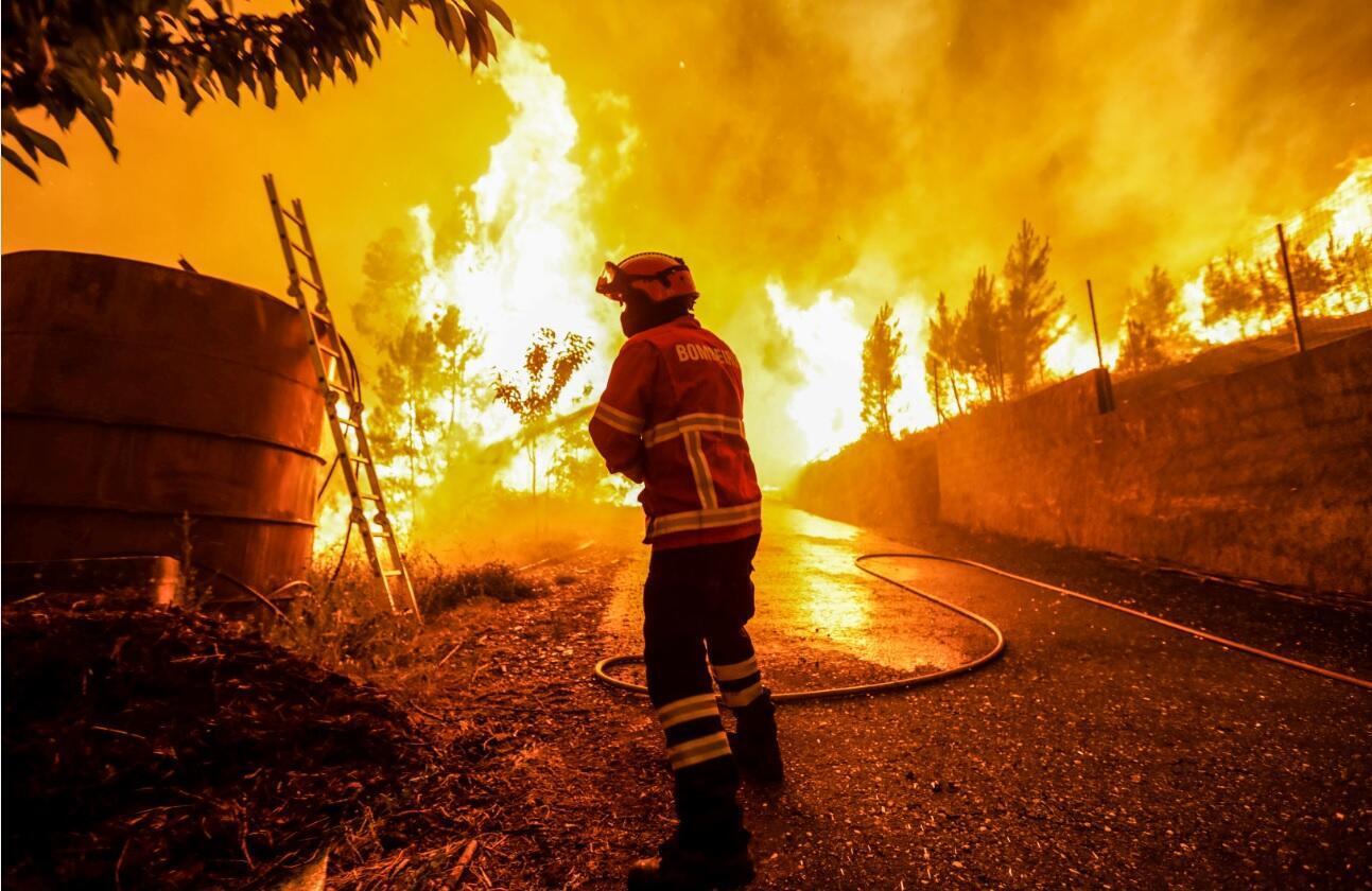 Bombeiros combatem as chamas junto às casas na aldeia de Pessegueiro, durante o incêndio florestal na Pampilhosa da Serra, 18 de Junho de 2017.