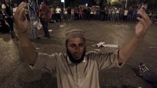 Un manifestant prie pendant les affrontements qui ont eu lieu au Caire ce samedi 23 juillet.