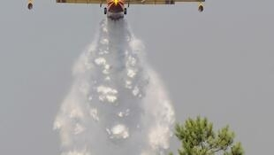 A firefighting tanker plane drops water on a forest fire near Lacanau earlier this month