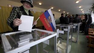 Eleitora vota em Bakhchisaray, na Crimeia, com bandeira da Rússia na mão.