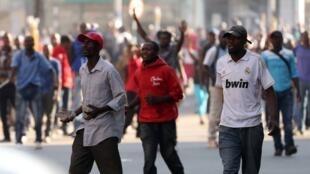 Umati wa wafuasi wa upinzani wa Movement for Democratic Change MDC) wakijibu baada ya askari kuwarushia risasi mbele ya makao makuu ya chama hicho, Harare, Zimbabwe Agosti 1, 2018.