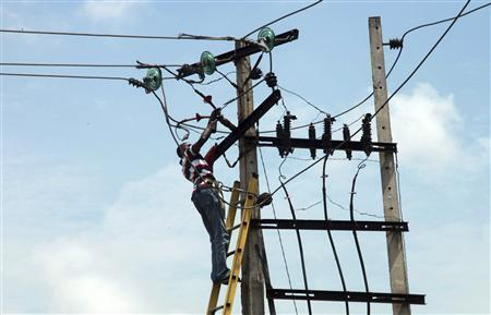 A power official works on an electric pole along a street in Lagos