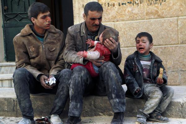 Un homme tient son bébé dans les bras après qu'il ait été sauvé de décombres causées par un bombardement, à Alep le 14 février 2014.