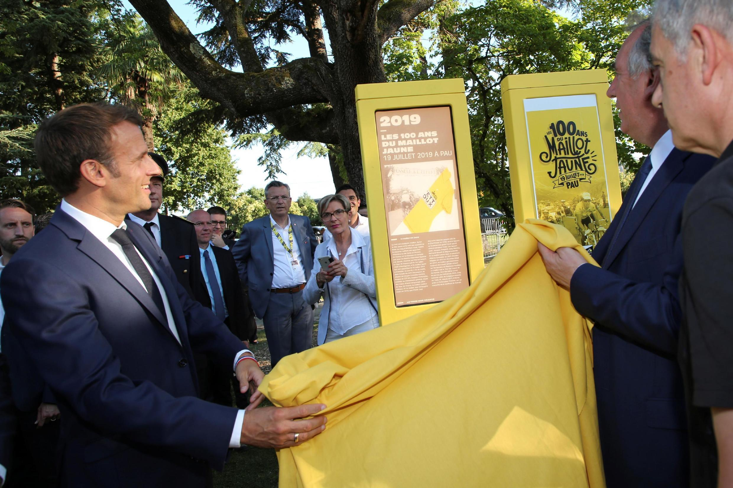 French President Emmanuel Macron unveils a plaque with the mayor of Pau, Francois Bayrou, to mark the 100th anniversary of the Tour de France yellow jersey, 19 July 2019.
