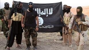 Members of IS in front of their flag