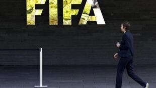 A member of staff walks past FIFA logo at their headquarters in Zurich, 27 May 2015